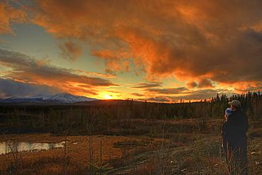 Couple watching sunset over Dawson Peaks, Teslin, Yukon