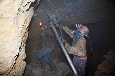 Miners drilling holes to place dynamite into the rock with a compressed air pneumatic drills in a shaft of the Cerro Rico de Potosi mine, Potosi Department, Bolivia