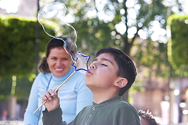 Boy blowing soap bubbles at Plaza de Armas (Plaza de los Murtires), Morelia, Michoacun, Mexico