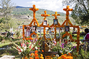 People decorate the grave of four children who died in a house fire for the celebration of Dia de los Muertos, the Day of the Dead at the Tzintzuntzan cemetery. People decorate the graves of their dead children, often referred to as little angels (angelitos) with offerings of flowers, particularly marigolds (cempoalxochitl or zempasuchil), bread of the dead (pan de muerto), candles, toys, the deceased's favourite food, drinks and personal belongings to guide their spirits home., Michoacun, Mexico