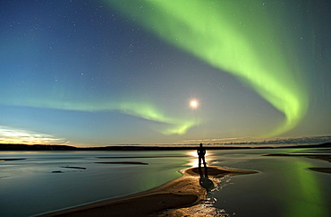 Person standing under an aurora borealis by the MacKenzie River, Fort Simpson, Northwest Territories, Canada