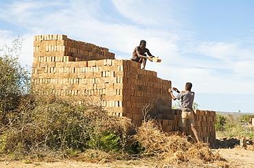 Men piling bricks for firing in Antsokay, Toliara Province, Madagascar