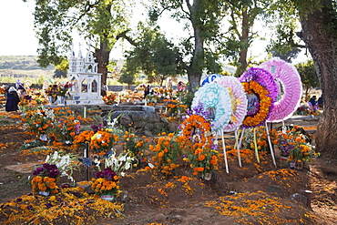 Celebration of Dia de los Muertos, the Day of the Dead at the San Andrus Tzirondaro cemetery. People decorate the graves of their loved ones with offerings of flowers, particularly marigolds (cempoalxochitl or zempasuchil), bread of the dead (pan de muerto), candles, the deceased's favourite food, drinks and personal belongings to guide their spirits home. Families celebrate their late relatives by the tombs on November 2, All Souls Day., Michoacun, Mexico