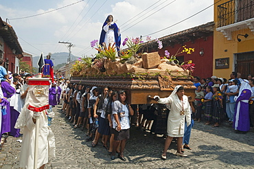 Women dressed in mourning carry the anda (float) of the Virgin Mary during the Procession of the Holy Cross on Good Friday in Antigua Guatemala, Sacatepuquez, Guatemala