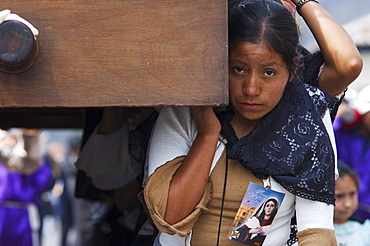 Woman dressed in mourning helps carry the anda (float) of the sorrowful Virgin Mary during a Good Friday Procession in Antigua Guatemala, Sacatepuquez, Guatemala