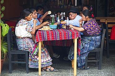 Maya family enjoying lunch at a restaurant, Santiago de Atitlun, Sololu, Guatemala