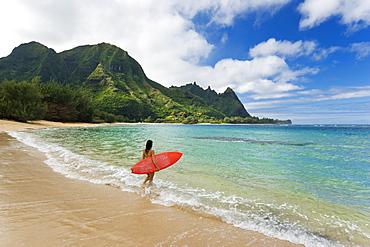 Hawaii, Kauai, Haena Beach Tunnels Beach, Woman entering ocean with surfboard.