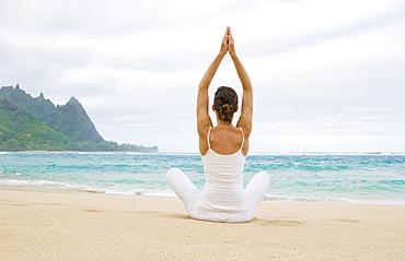 Hawaii, Kauai, Haena Beach Tunnels Beach, Woman meditating on sandy shore.