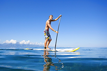 Hawaii, Maui, Paia, Athletic stand up paddle surfer in Maui's North Shore