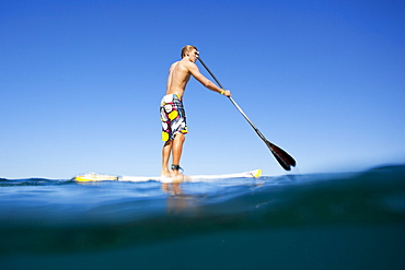 Hawaii, Maui, Paia, Athletic stand up paddle surfer in Maui's North Shore, over-under shot