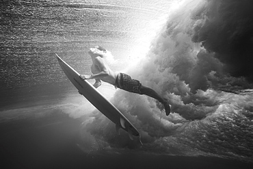 Indonesia, Bali, Surfer duck dives under wave, view from underwater, black and white
