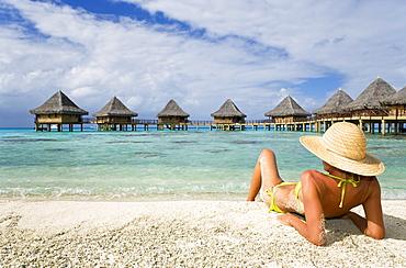 French Polynesia, Tuamotu Islands, Rangiroa Atoll, Woman lounging on beach, Luxury resort bungalows in background.