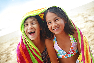 Hawaii, Oahu, Two young girls wrapped in a colorful towel.