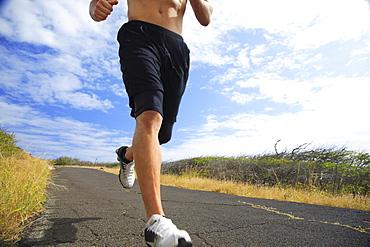 Hawaii, Oahu, Makapu'u, Athletic male running along the makapuu hiking trail, closeup of feet