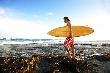 Hawaii, Oahu, young man walking on rocky coastline with surfboard