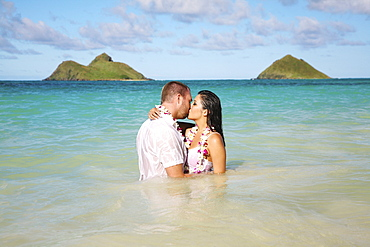 Oahu, Hawaii, Lanikai, Young couple both holding eachother and kissing.