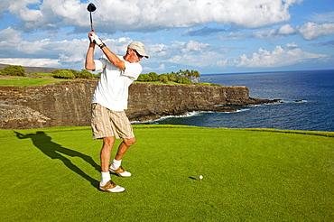 Hawaii, Lanai, Manele Golf Resort, Man tees off with Ocean view.