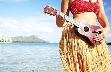 Hawaii, Oahu, Waikiki, Hula dancer playing ukulele along beach - close-up of midriff, Diamond Head in the distance.