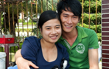 South East Asia, Vietnam, Hanoi, Student couple relaxes on college campus for their portrait.