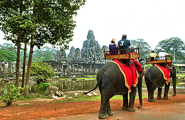 South East Asia, Cambodia, Siem Reap, Tourists take a guided elephant tours to ancient Banyon Temple.