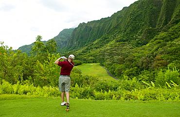 Hawaii, Oahu, Honolulu, Ko'olau Golf Course, Man tees off at the fifteenth hole.