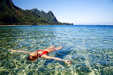 Hawaii, Kauai, Tunnel's beach, Woman floats in the ocean.