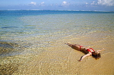 Hawaii, Kauai, Kealia beach, Woman laying on the beach in the shoreline.