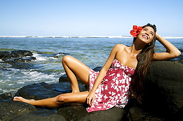 Hawaii, Kauai, Anini beach, Attractive young woman on the rocks with hawaiiana attire.