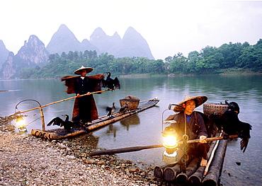 China, Li River, near Yangshou, Local men floating on bamboo raft.