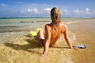 Hawaii, Kauai, Tunnels beach, A woman wearing yellow and blue fins on beach.