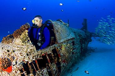 Hawaii, Oahu, Male diver exploring World War II Corsair fighter plane wreck.