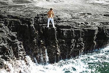 Hawaii, Oahu, Male wearing white pants on rocky cliff.