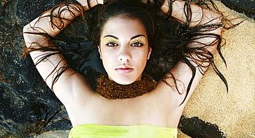 Oahu, Hawaii, Headshot portrait of a beautiful girl laying on the rocks near the sand.