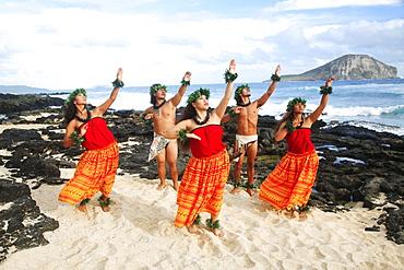 Hawaii, Oahu, Makapu'u Beach, Group of Tahitian Male and Female Dancers posing, Rabbit Island in background.
