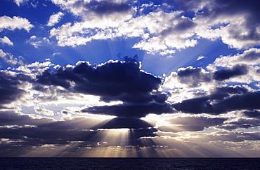 Hawaii, Late afternoon rain clouds over ocean horizon.