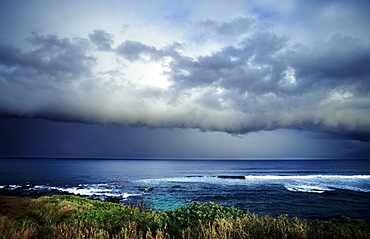 Hawaii, Maui, North Shore, Storm front clouds overlooking ocean from hillside.