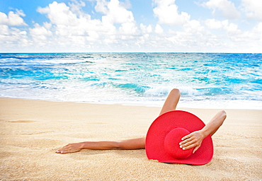 Hawaii, Woman laying on the beach in remote tropical location.