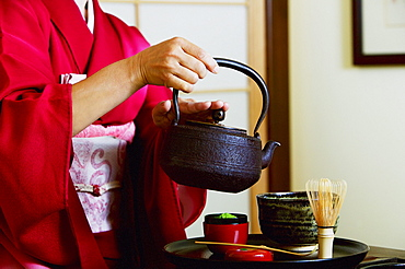 Close up of geisha pouring tea at tea ceremony.