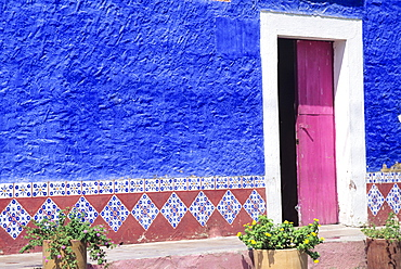 Mexico, Contrasting colorful restaurant wall with hand painted trimming.