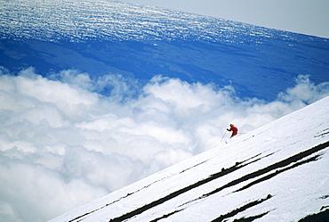 Hawaii, Big Island, Mauna Kea, Woman skiing downhill at high elevation.