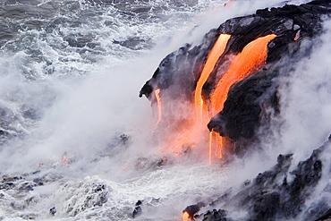 Hawaii, Big Island, near Kalapana, Pahoehoe lava flowing from Kilauea into frothy Pacific Ocean.