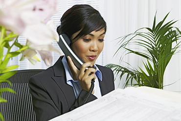 Asian businesswoman in office on phone.