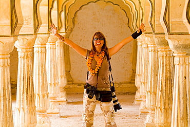 India, Rajasthan, Jaipur, Female tourist with lots of cameras at Amber Fort.
