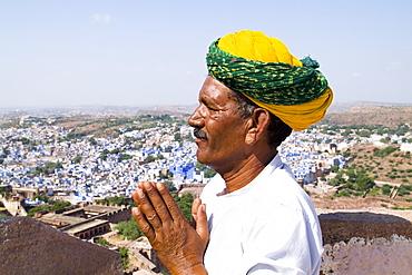 India, Rajasthan, Jodhpur, Hindu man praying at Fort Mehrangarh overlooking blue city.