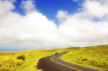 Hawaii, Big Island, South Kohala, Car driving down Saddle Road which curves through rolling grass hills near Waikii Ranch.