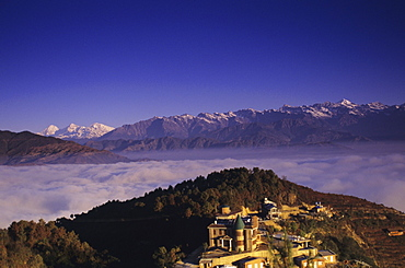 Nepal, Nagarkot, overview of Niva Lodge on hillside, cloud line and Himalayan range in background.
