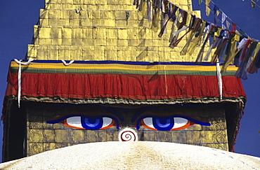 Nepal, Kathmandu, close-up of painted eyes on Boudhanath Stupa, colorful streaming flags.