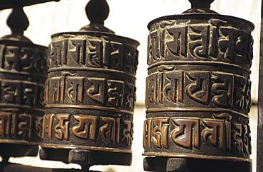 Nepal, Kathmandu, Swayambhunath Temple, closeup of prayer wheels with carvings.