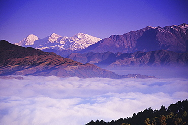 Nepal, Nagarkot, distant view of central Himalayas from hillside, cloud cover below, purple dusky lighting.