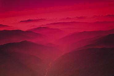 Nepal, Kathmandu Valley, river flowing between mountains at sunset, red foggy glow.